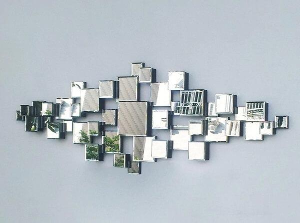 O espelho quadrado pequeno forma uma obra de arte na parede