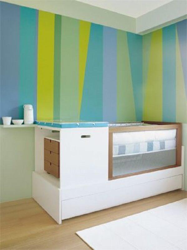 O papel de parede se destaca nessa decoração com berço com gaveta