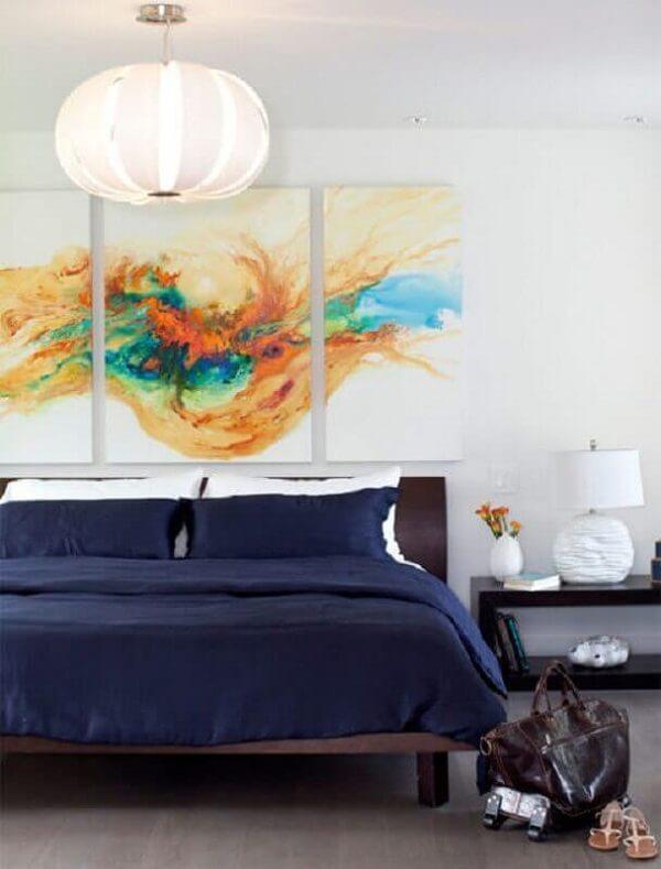 O quadro abstrato colorido foi posicionado sobre a cabeceira da cama
