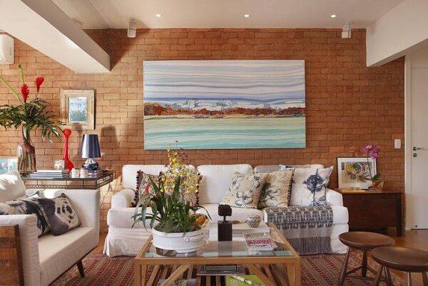 O quadro colorido faz o contraste perfeito com a parede de tijolinho