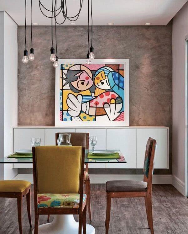 O quadro colorido posicionado sobre o aparador é o grande destaque do ambiente