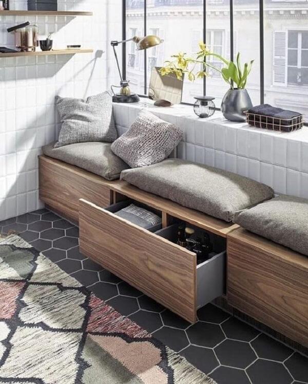 O sofá baú de madeira ajuda na organização do cômodo