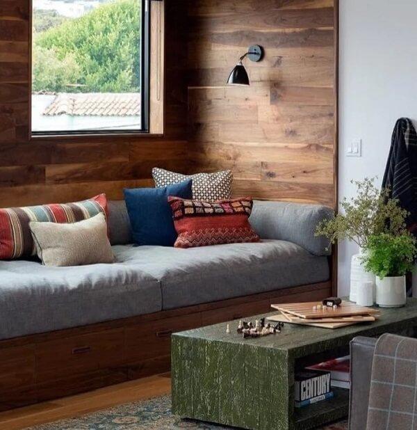 O sofá baú de madeira embutido na parede é uma ótima alternativa para espaços pequenos