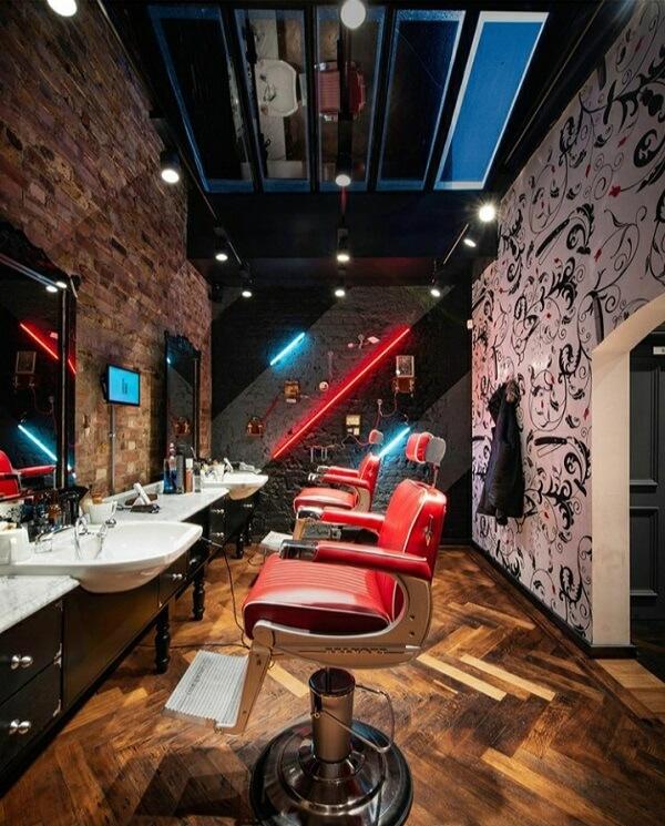 O vermelho das cadeiras se destacam nessa decoração de barbearia