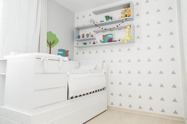 Quarto com papel de parede em formas geométricas e o berço com gavetas embutidas