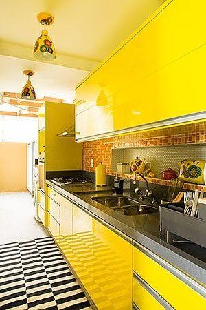 Armário de cozinha amarelo com tapete preto e branco