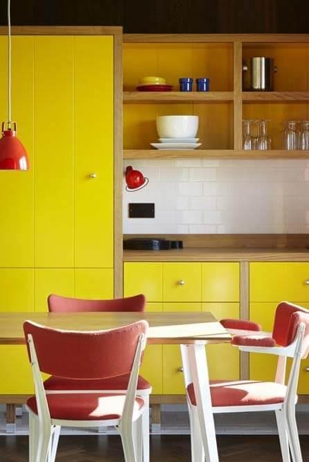 Armário de cozinha amarelo com cadeiras vermelhas