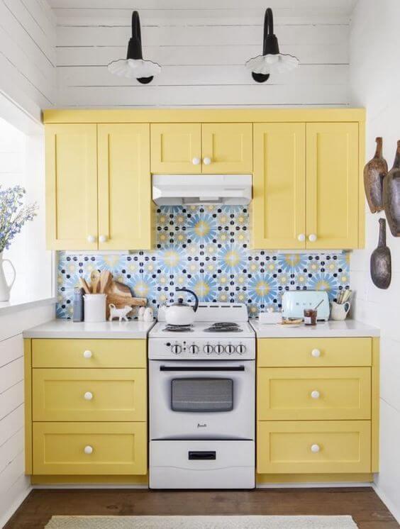 Revestimento azul com armário de cozinha amarelo pastel