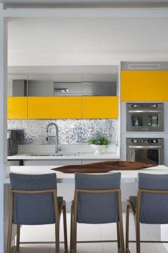 Armário de cozinha amarelo com bancada branca e cadeiras cinza