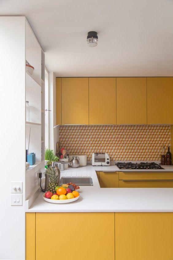 Armário de cozinha amarelo e branco com revestimento combinando com a paleta de cores