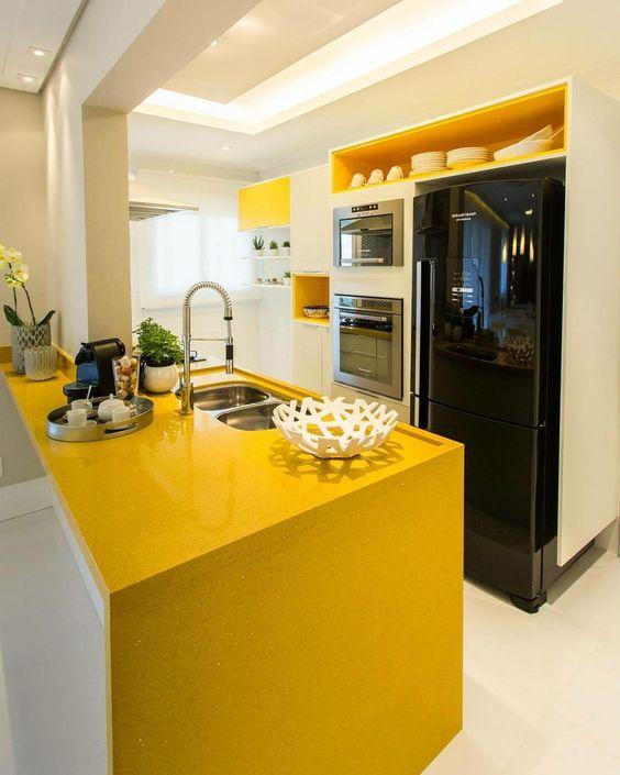 Bancada de cozinha amarela com armários brancos