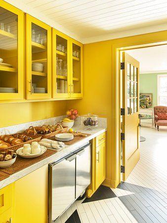 Armário de cozinha amarelo e parede da mesma cor