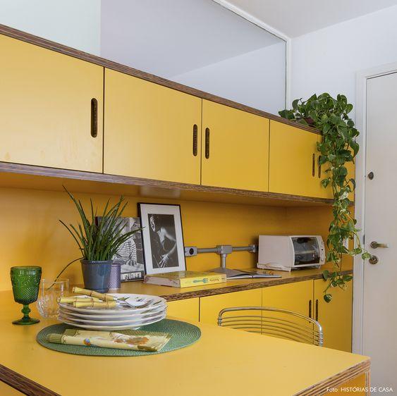 Armário de cozinha amarelo decorado com plantas