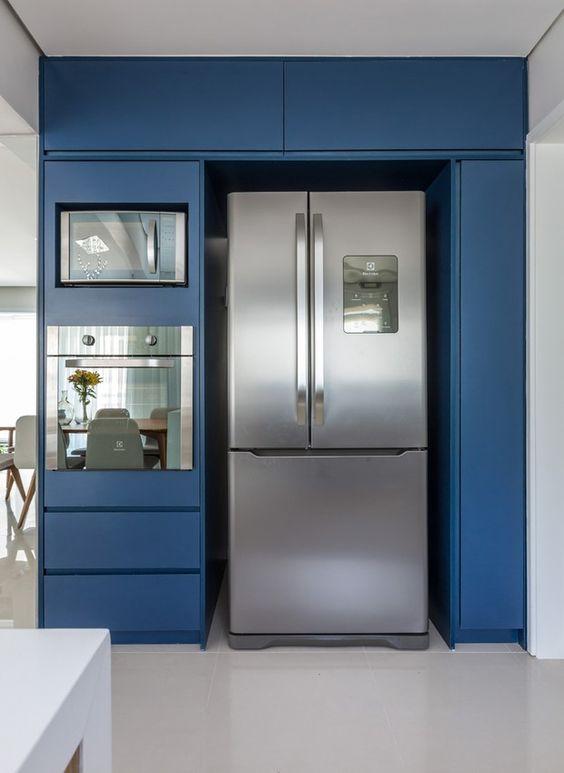 Cozinha pequena azul com torre quente ao lado da geladeira