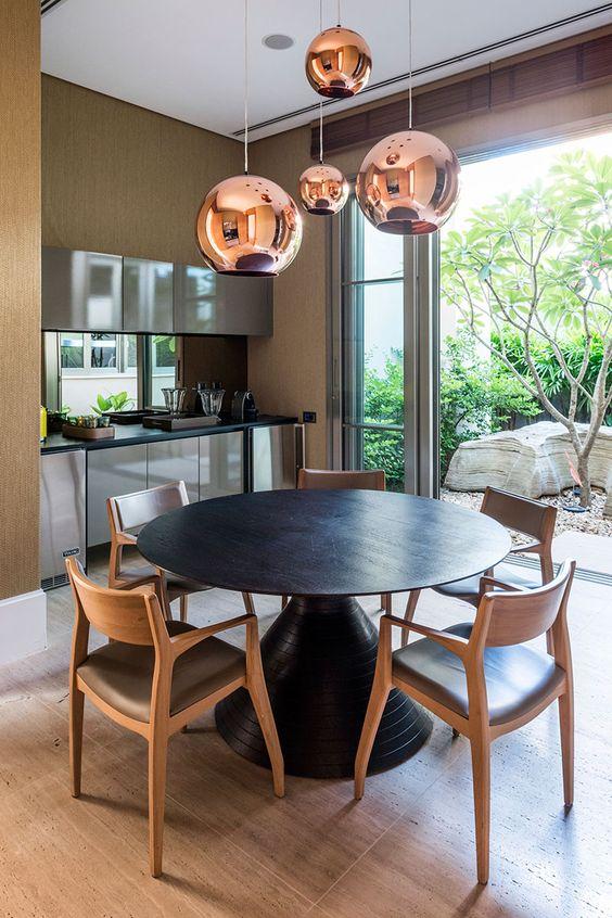 Varanda com mesa de jantar preta e cadeiras de madeira