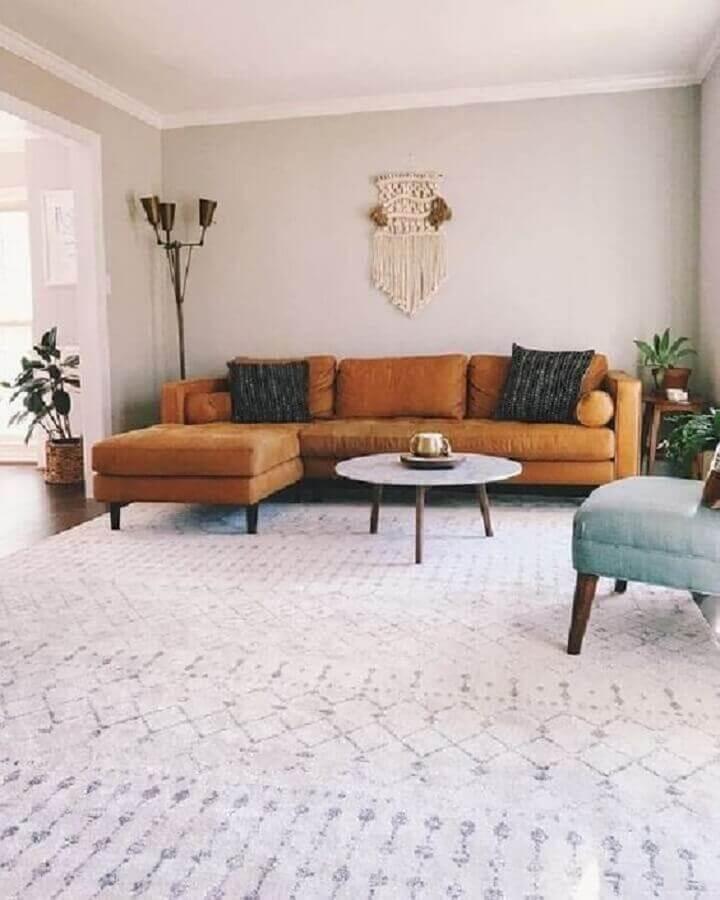 decoração clean para sala com mesa de centro redonda e sofá marrom com chaise Foto Pinterest