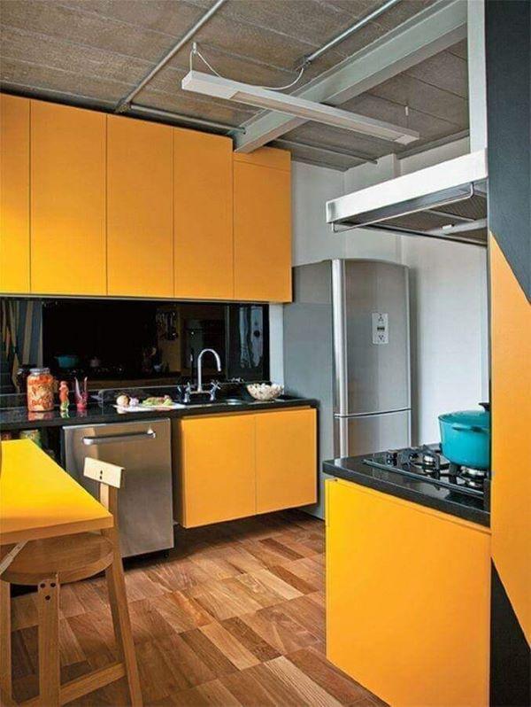 Armário de cozinha amarelo e preto com piso laminado