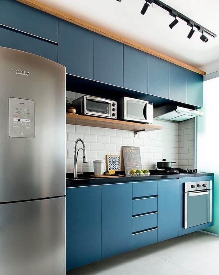 decoração com armário de cozinha planejado azul com prateleira de madeira  Foto Jeito de Casa
