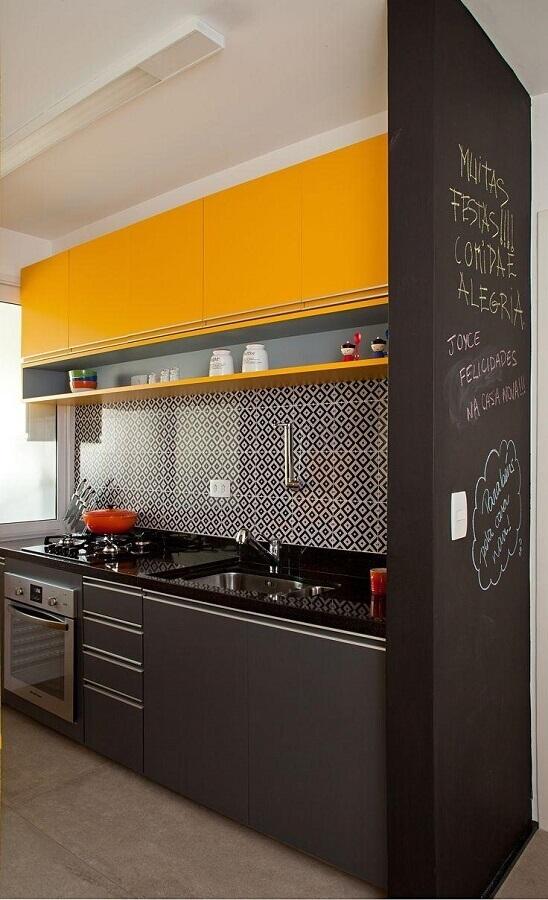 Armário de cozinha amarelo e preto com parede de lousa