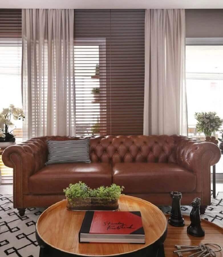 decoração de sala com sofá de couro marrom chesterfield e mesa de centro redonda  Foto Estúdio AE Arquitetura
