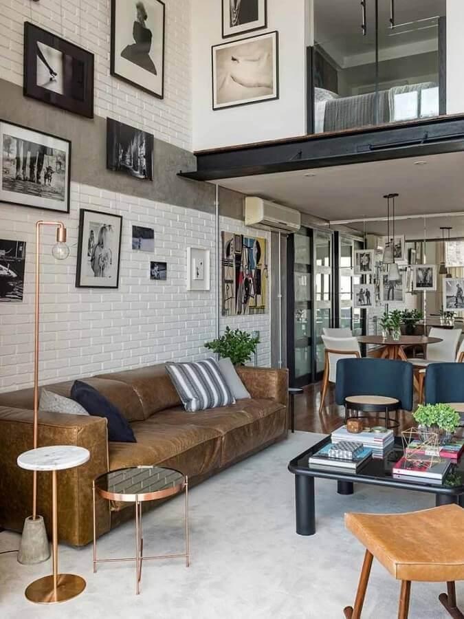 decoração de sala moderna com vários quadros e sofá de couro marrom  Foto JA Interiores