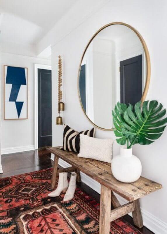 decoração hall de entrada com espelho redondo e banco de madeira rústica Foto domino magazine