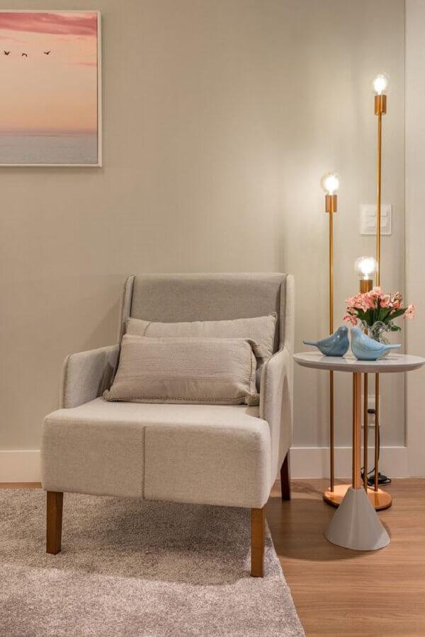 Decoração moderna com poltrona cinza e luminária de chão dourada