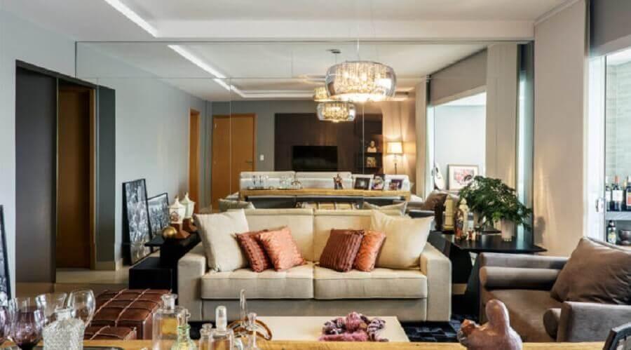 decoração sala de estar com parede espelhada e lustre pendente de vidro Foto Cioli Arquitetura