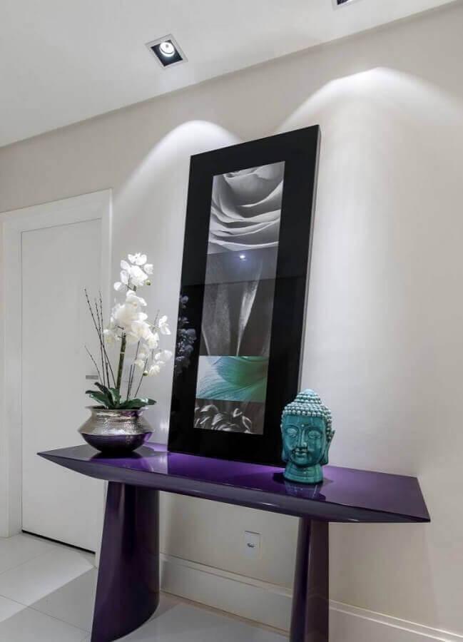 decoração simples para hall de entrada com espelho preto apoiado em aparador roxo Foto Pinterest