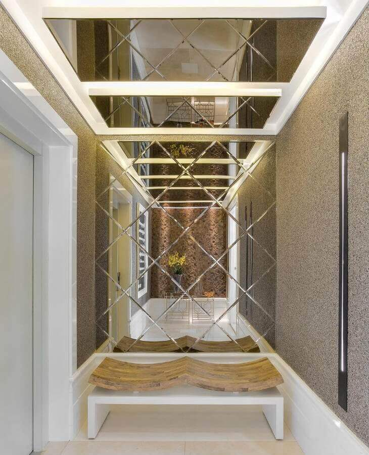 decoração sofisticada com parede espelhada para hall de entrada pequeno Foto Enrique Moreira Arquitetura