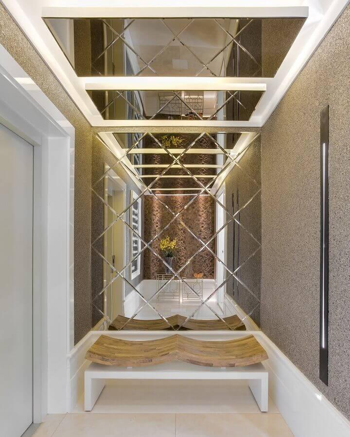 decoração sofisticada para hall de entrada com espelho grande em parede planejada  Foto Erique Moreira Arquitetura