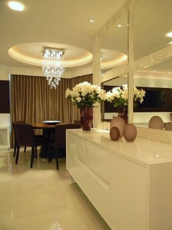 decoração sofisticada para sala de jantar com buffet branco suspenso e espelho de parede bisotado Foto Lolafá