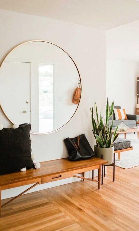 hall de entrada decorado com banco de madeira e espelho grande de parede redondo Foto Home Fashion Trend
