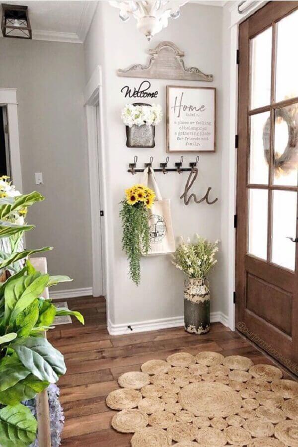 Hall de entrada simples e pequeno decorado com tapete sisal redondo e ganchos de parede Foto Hobby Lobby