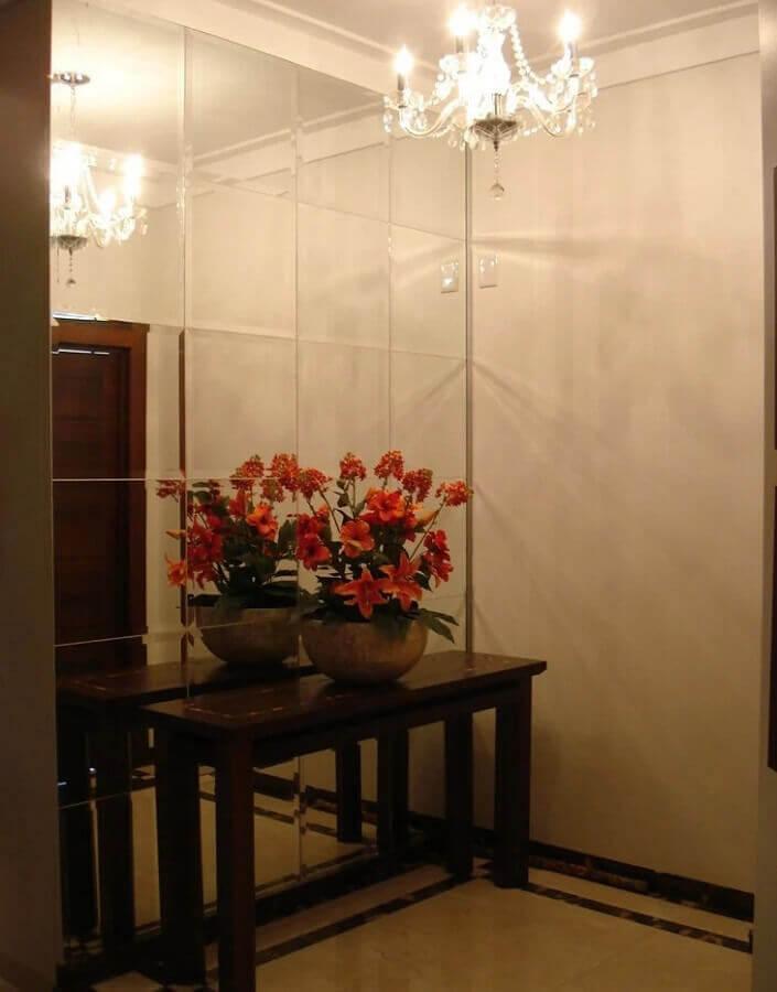 lustre de cristal e aparador de madeira para hall de entrada pequeno decorado com parede espelhada Foto Paves Arquitetura