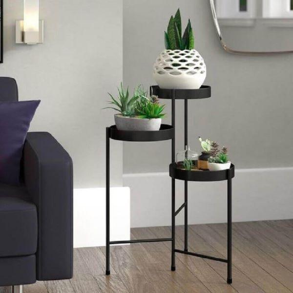 Mesa lateral alta preta decorada com vasos de plantas