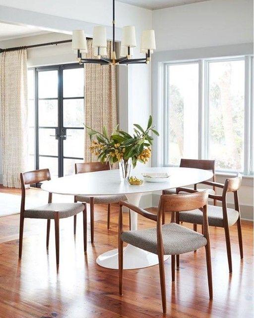 Mesa oval branca com cadeiras de madeira