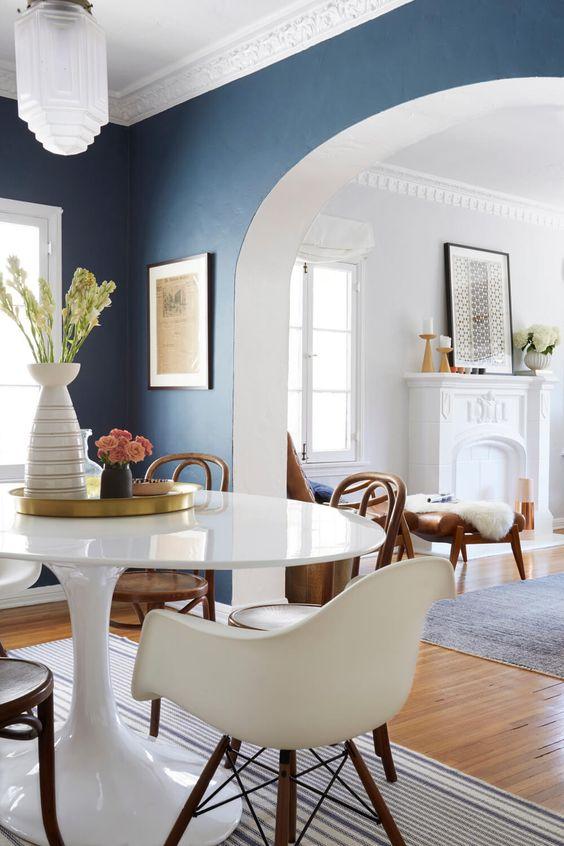 Mesa oval pequena e branca na sala de jantar azul