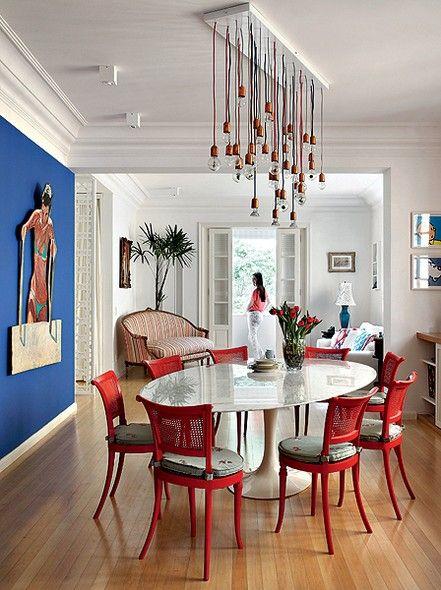 Mesa oval com cadeiras vermelhas na sala colorida
