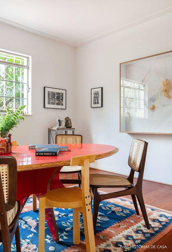 Mesa oval vermelha com cadeira de madeira