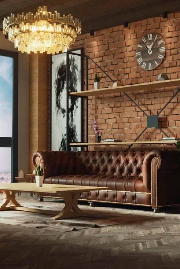 modelo diferente de lustre pendente redondo para sala com sofá marrom chesterfield e parede de tijolinho Foto Apartment Therapy