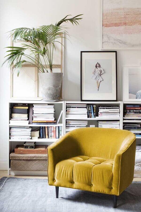 poltrona colorida amarela para sala decorada com estante baixa para livros  Foto Planeta Design