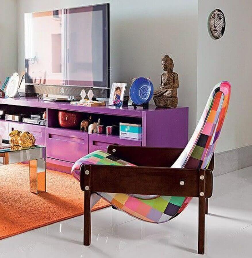 poltrona colorida de madeira para sala decorada com tapete laranja e rack roxo Foto Jeito de Casa