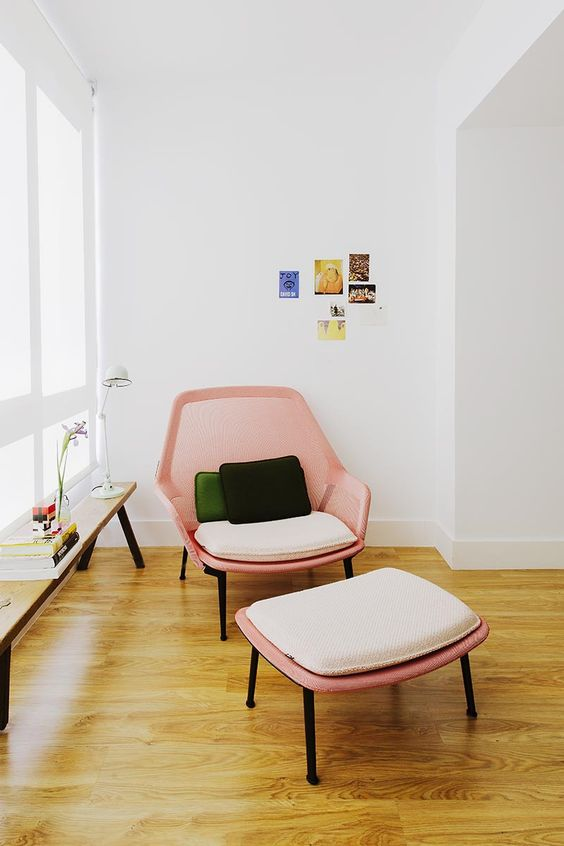 Poltrona cor de rosa com puff para cantinho da leitura na sala iluminada