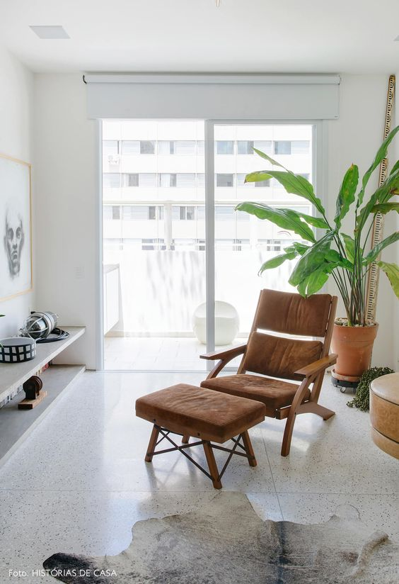 Poltrona com puff marrom na sala de estar aconchegante