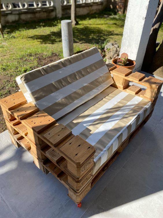 Poltrona de pallet com estofado listrado para varanda de casa