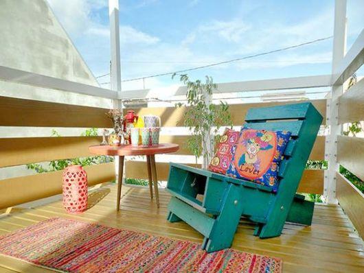 Varanda colorida com poltrona feita de pallet
