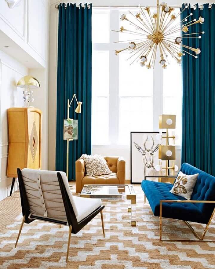 poltrona para sala colorida decorada com lustre pendente moderno e sofá azul Foto The Fashion Hall