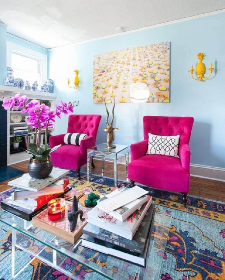 sala azul decorada com poltrona rosa pink e mesa de centro de vidro Foto Apartment Therapy