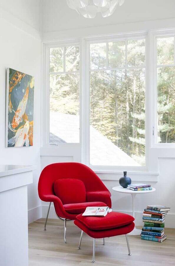 sala branca decorada com poltrona colorida vermelha com puff  Foto LDa Architects